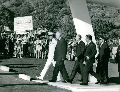 Charles De Gaulle is walking with the officers.