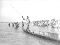 Senegal people standing in the beach with a man rowing a boat.