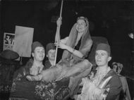 Viola Aberle is carried in to the Opera Masquerade on a flying carpet by her fez adorned entourage.