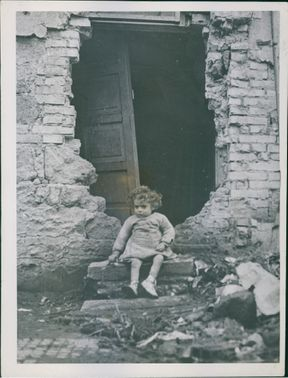 A two-year-old Italian child, Ignazzio Virzi, sits on the shell-splintered front stoop of the two-room Virzi home in Aprilla, Italy.