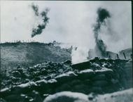 Smoke from the blast and firing during the war, soldiers hiding in the trench.