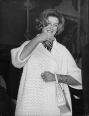 Photo of Princess Alexandra with a bag, smiling.