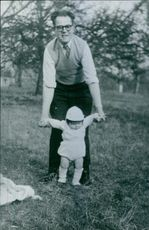 Man standing in the park, holding a baby, teaching her to walk.