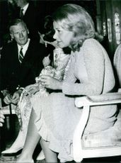 A vintage photo of Athina Livanos sitting in a chair while holding her cigarette taken in June 12, 1972.
