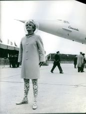 Woman standing and smiling, beside the airplane.
