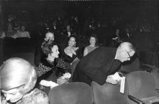 The Duke and Duchess of Windsor in a theater. The Duke look at the name tag on the seat.