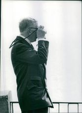 A photo of an old man standing and holding a camera taking pictures.
