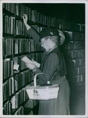 A woman getting book at the library. 1935.