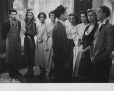 A man looking at the people standing in a row, in a still from a movie.