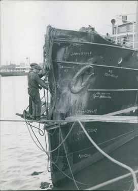 Two workmen stands on the wooden platform as they fix the ship.