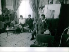 Man and women from The Lao Royal Family siting in home, talking on telephone.