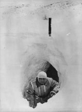 A man getting out of a snow-cave.