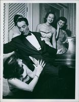Women watching Victor Borge play his piano.