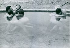 Men and women grouped together and hugging each other while in a pool of water.