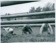 Men kneeling and trying to hide.   1958  Conditioners Straning Il. TRW man on the road for the log, in the rain.