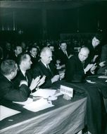 Gaston Defferre being applauded by men in a conference room. 1964
