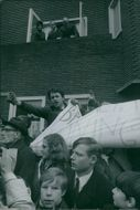 People with banner at baptism of son of Princess Margriet of the Netherlands and Pieter van Vollenhoven, 1970.