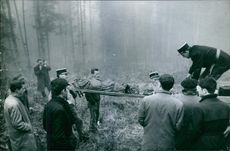 People helping the soldiers to load a dead body into the vehicle in forest.