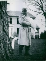 A portrait of Victor Borge standing and holding a duck.