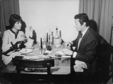 Michel Auclair and Belzy Roset  enjoying a meal while having a conversation, 1964.