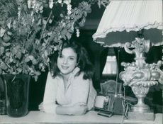Sandra Milo leaning on table at her home.