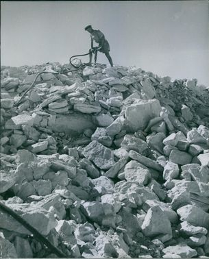 A soldier digging in rock land with machine.