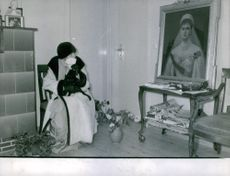 Anastasia Nikolaevna sitting alone on chair and looking at the portrait of a woman.