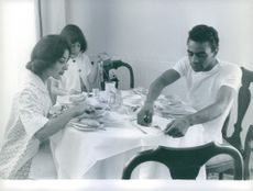 American singer Johnny Mathis enjoying a meal with his friend named Beverly Pauls who has a girl Sherly, 1961.
