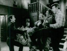 Four men singing and dancing under the staircase.