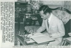 King Bhumibol Adulyadej signs a draft for Thailand's new constitution