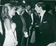 Prince Charles of Wales talks with Carol White and Tommy Steele during a gala premier.