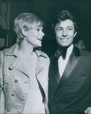 Sally Kellerman and George Chakiris talking to each other and smiling during a party.