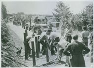 Steel road blocks, set up by retreating Germans at the outskirts of Brest, are cleared by French civilians to speed the advance of American Army vehicles. Some liberated French are siding the allies by repairing bridges and roads, while others are fightin