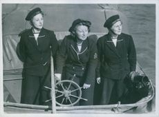 """Coxswain and two in """"seaman"""" in their craft in the Harbour. 1943."""