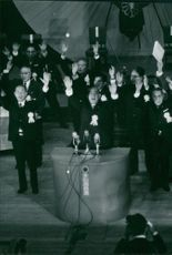 Japanese politicians raising their hands during a conference.