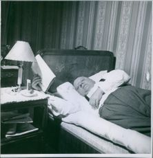 Man lying on the bed, reading newspaper.
