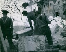 A polish officer guard supervises German P.O.W. as they lever huge blocks of masonry from amidst the ruins.