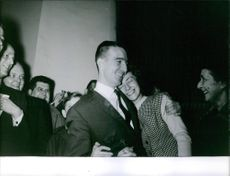 Man and woman hugging, while other people smiling and cheering, 1962.