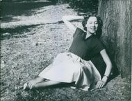Woman leaning on tree.