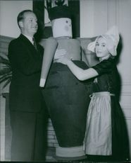 Man and woman with sculpture, smiling.