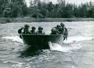 Soldiers in motorboat, heading.