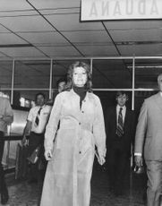 Rita Hayworth wearing an over-coat, coming out of airport.