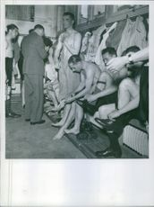 Men getting ready in the dressing room, wearing shoes. 1939