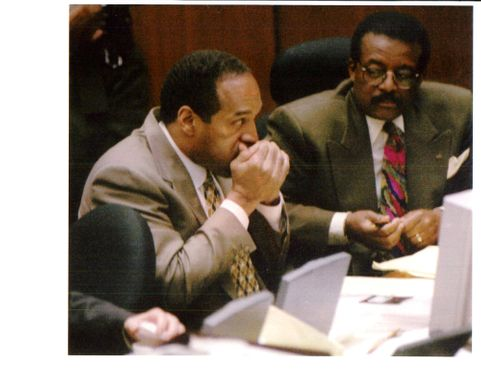 Defendant O.J Simpson cups his hands to his mouth keep warm.
