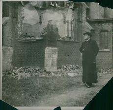Vintage  photo of a man standing on a ruin place. 1914