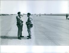 Two military officers having a conversation on the runway of a military base in Kuwait.