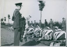 A military officer holding a funeral flower stands ifront lined caskets where soldiers stood, 1944
