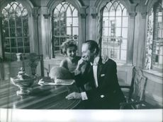 """Kay Kendall sitting at the dining room with Sir Reginald Carey """"Rex"""" Harrison. 1959."""
