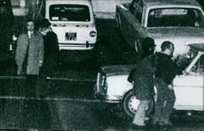 Vehicles being parked with people walking on the sidewalk, 1971.