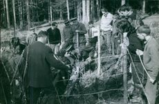 A group of people, officers and civilian, investigating something hidden in the ground, 1964.